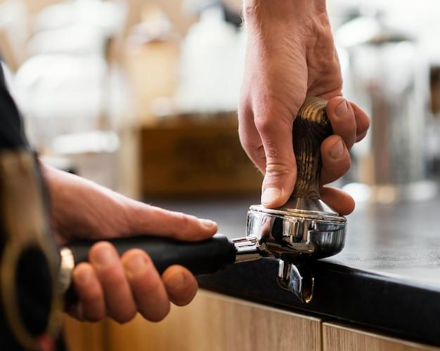 Sluit omhoog handen die koffiebonen malen