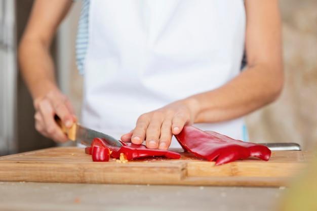Sluit omhoog handen die paprika snijden
