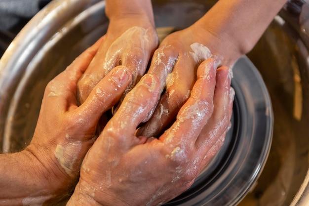 Sluit omhoog handen die samen aardewerk doen