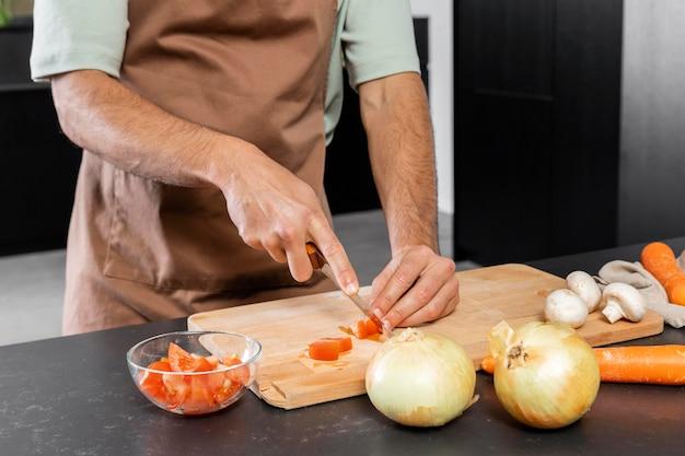 Sluit omhoog handen die tomaat snijden