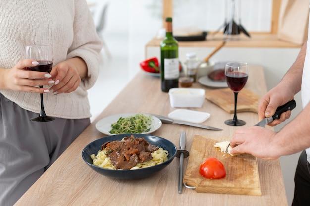 Sluit omhoog handen die voedsel met mes snijden
