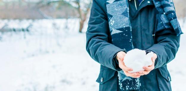 Sluit omhoog handen houdend sneeuw op een de winterdag in openlucht