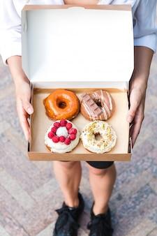 Sluit omhoog handen houdend vier stukken totaal verschillende kleurrijke en heerlijk uitziende donuts in ecologische kartondoos