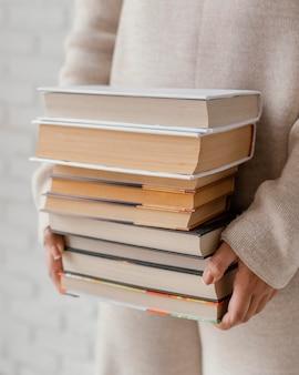 Sluit omhoog handen met boekenstapel