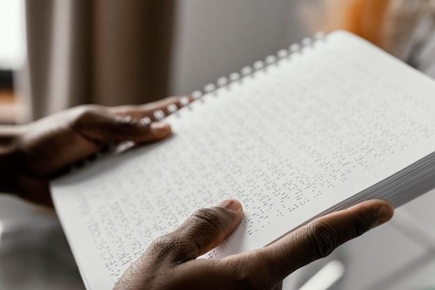Sluit omhoog handen met braille-notitieboekje