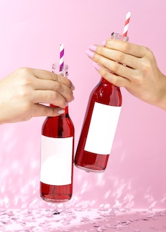 Sluit omhoog handen met flessen en rietjes