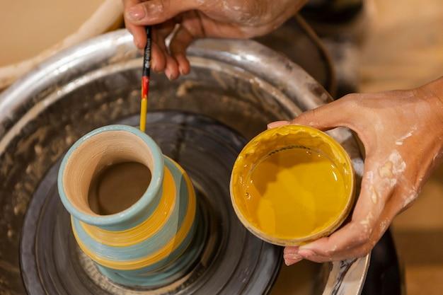 Sluit omhoog handen met gele verf