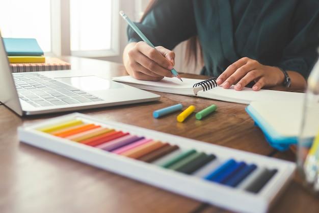 Sluit omhoog handen met pen schrijvend op notitieboekje.