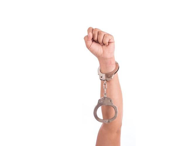 Sluit omhoog handen met zilveren die handcuffs op witte achtergrond worden geïsoleerd