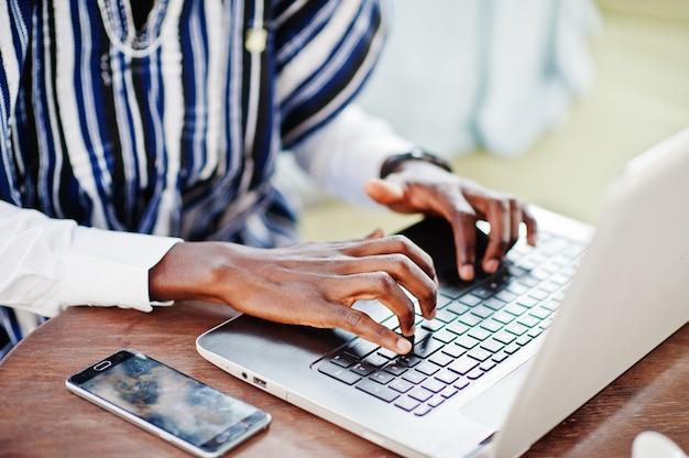 Sluit omhoog handen van de afrikaanse mens in traditionele kleren die achter laptop en het werken zitten