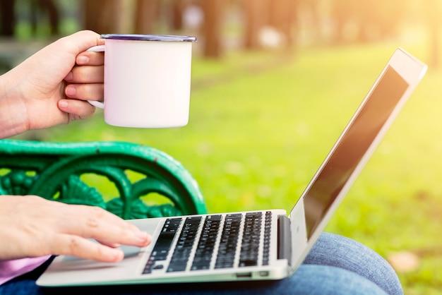 Sluit omhoog handen van een vrouw die een kop van koffie houdt. meisje met behulp van een laptop in de ochtend.