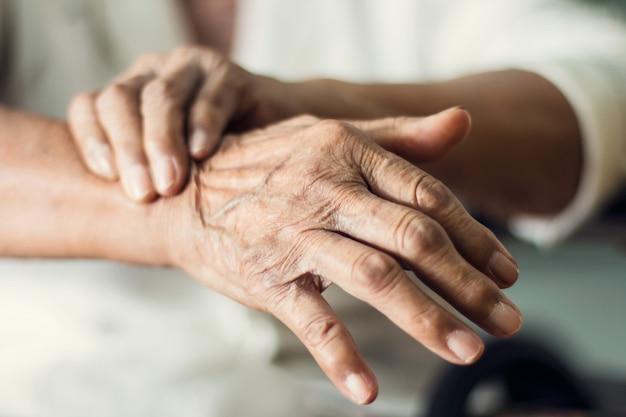 Sluit omhoog handen van hogere bejaardepatiënt die aan de ziektesymptoom van pakinson lijden