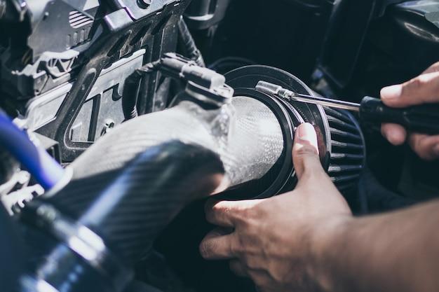 Sluit omhoog handen van onherkenbare werktuigkundige die de autodienst en onderhoud doen. luchtstroom veranderen
