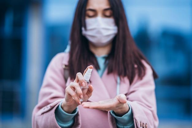 Sluit omhoog handen van wijfje in medisch masker die haar handen met ontsmettingsmiddel schoonmaken openlucht in de stad om virusziekten te voorkomen. coronavirus, covid-19, epidemie, pandemie, quarantaineconcept.