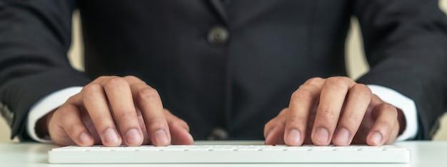 Sluit omhoog handen van zakenman die zwart kostuum dragen typend draadloos wit toetsenbord. de kopbal van bedrijfs aziatische kerel schrijft e-mail op computerpc in het concept van manager, uitvoerende of professionele wetsmensen.