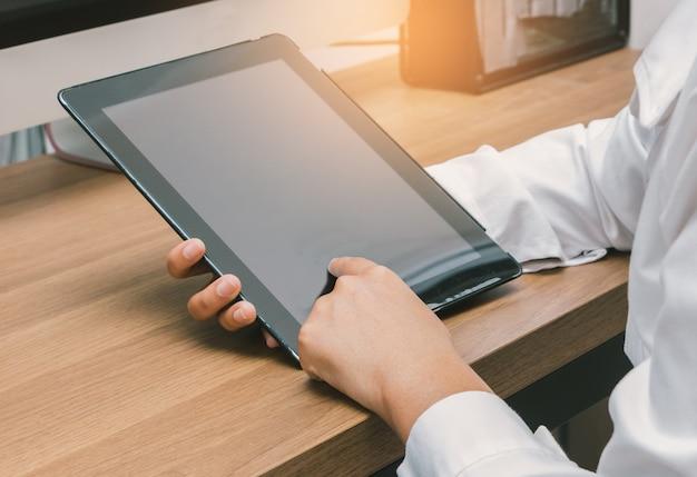 Sluit omhoog handen wat betreft het scherm van bedrijfsvrouw die tablet op haar bureau gebruiken