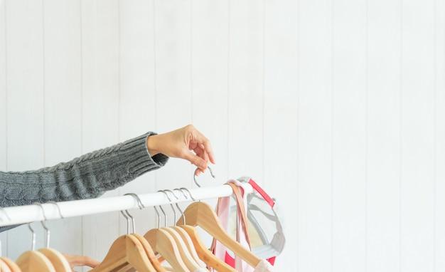 Sluit omhoog handvrouw die kleren in kleedkamer kiezen. schoonheid en mode concept.