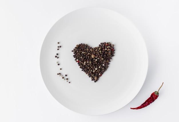 Sluit omhoog hart dat van geïsoleerde zwarte peperkorrels wordt gemaakt