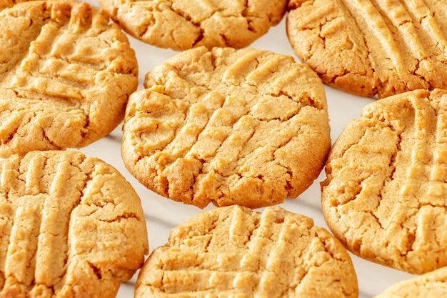 Sluit omhoog heerlijke eigengemaakte pindakaaskoekjes op koelrek. witte ruimte. gezond snackconcept. macro foto.
