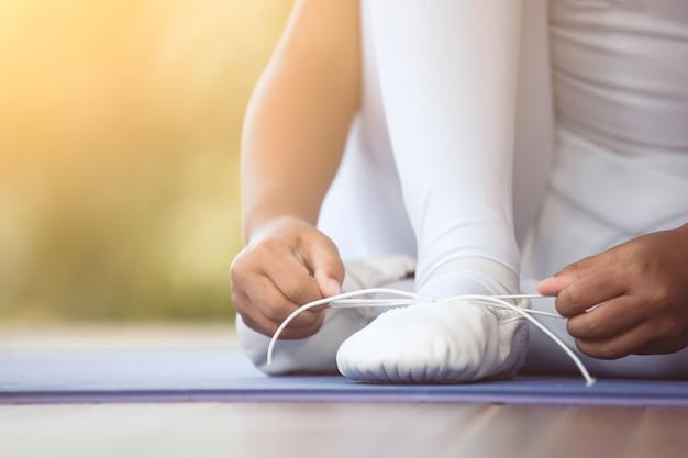 Sluit omhoog het aziatische kindmeisje binden op voeten pointe schoenen die voor het praktizeren van een ballet voorbereidingen treffen