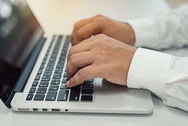 Sluit omhoog het bedrijfsmens typen op laptop op bureau, huisbureau