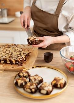 Sluit omhoog het dessert van de chef-kokholding