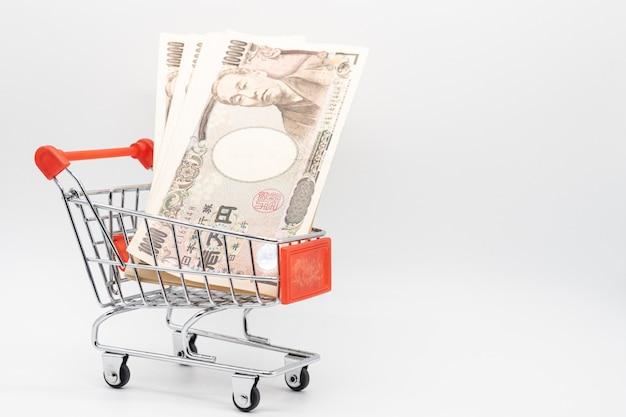 Sluit omhoog het geldbankbiljet van de muntyen in klein het winkelen karretje. japan economie en online markt.