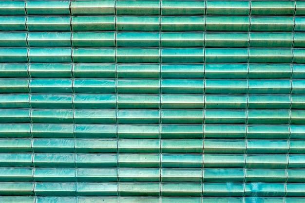 Sluit omhoog het glanzende turkooise groene blok van de de structuurlaag van de tegelkleur