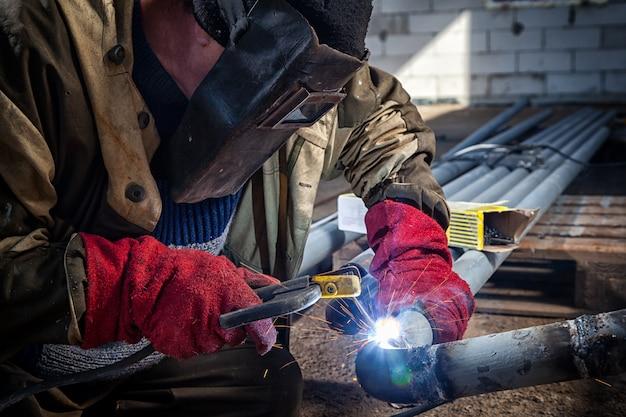 Sluit omhoog het metaalpijp van de lasserslas bij bouwwerf