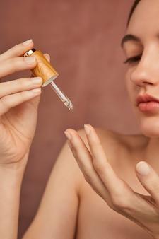 Sluit omhoog het serum van de vrouwenholding