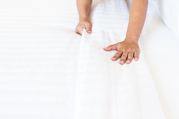 Sluit omhoog het witte bedblad van de handopstelling in hotelruimte