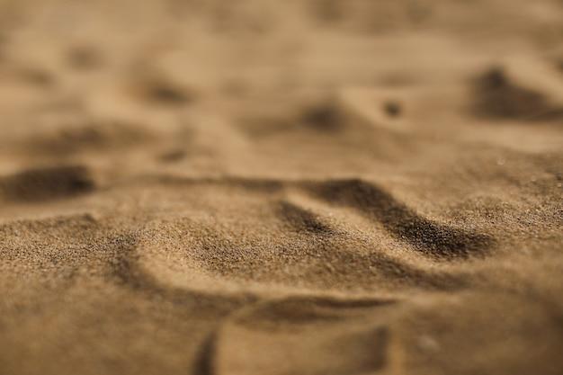 Sluit omhoog het zand zachte textuur van het aardstrand in de zomer. selectieve aandacht