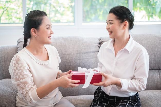 Sluit omhoog hogere vrouwenmensen verzend de verrassing van de giftdoos haar ouders met giftdoos. de verjaardagskerstmis van de in dozen doende dagvakantie en het concept van de moederdag
