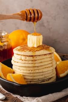 Sluit omhoog honing die van dipper over pannekoeken druipen