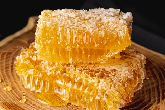 Sluit omhoog honingraten op houten schotel