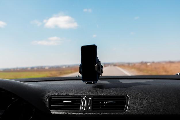 Sluit omhoog houder van de auto de slimme telefoon
