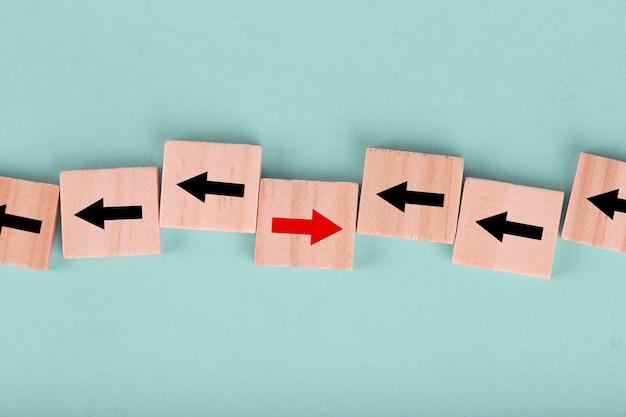 Sluit omhoog houten blok op blauw met rode pijl die de tegenovergestelde richting zwarte pijlen onder ogen zien