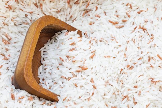 Sluit omhoog houten kop op witte rijstmengeling met rode rijstachtergrond.