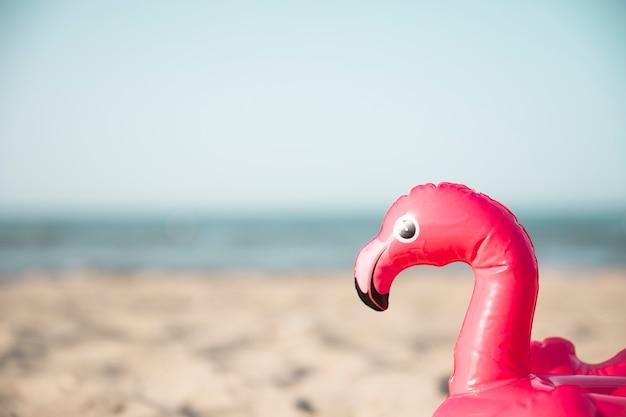Sluit omhoog inflatble de flamingo zwemt ring op strand Gratis Foto