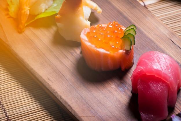Sluit omhoog japans voedsel, sushireeks en theepot die met sakura op de houten lijst wordt geplaatst