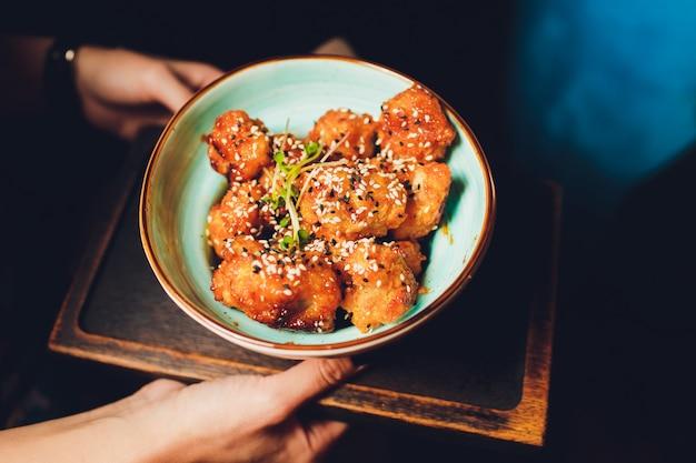 Sluit omhoog japanse sushi op een zwart dienblad en verkoop bij de nachtmarkt met donkere achtergrond.