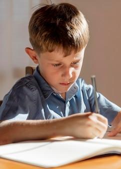 Sluit omhoog jong geitje dat op notitieboekje schrijft