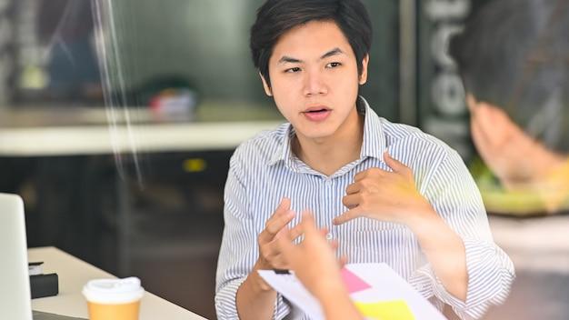 Sluit omhoog jong mannetje die aan collega's spreken die in modern bureau raadplegen.