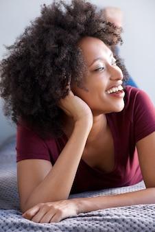 Sluit omhoog jonge afrikaanse op vloer thuis liggen en vrouw die glimlachen