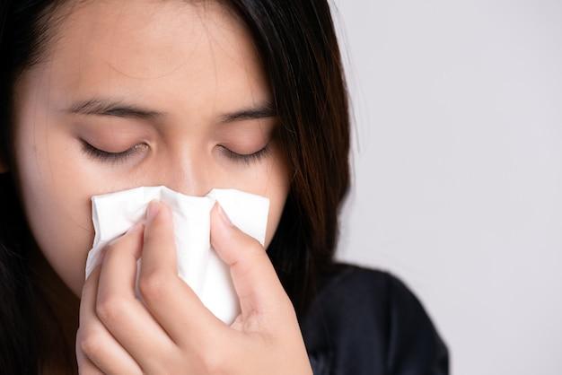 Sluit omhoog jonge aziatische vrouw werd ziek, griep en neusallergie niezend in een weefsel