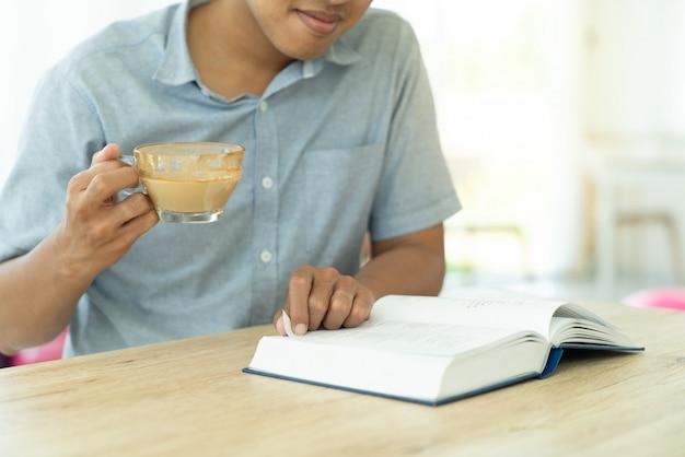 Sluit omhoog jonge mens die een boek voor verhoging van kennisonderwijs lezen tijdens hebben een koffie in koffie