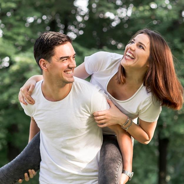 Sluit omhoog jonge mens die zijn smileymeisje vervoeren