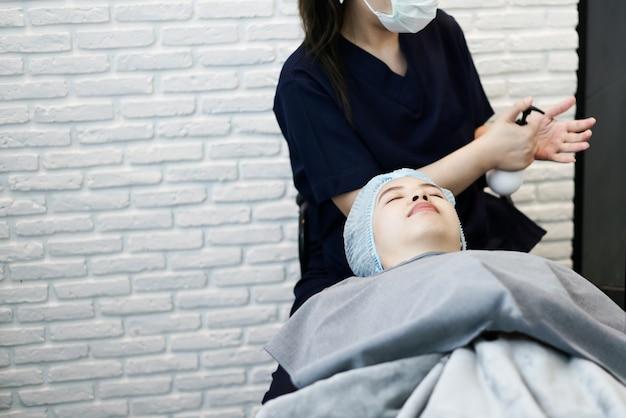 Sluit omhoog jonge vrouw die gezichtsbehandeling wachten. plastische esthetische gezichtschirurgie in schoonheidskliniek.