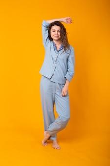 Sluit omhoog jonge vrouw in blauwe huiskleding. geïsoleerd op gele achtergrond. pyjama concept.