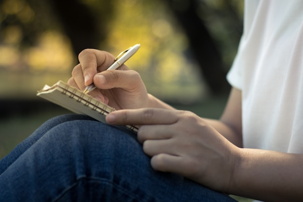 Sluit omhoog jonge vrouwen die op notitieboekje in park, concept in onderwijs en kennis schrijven